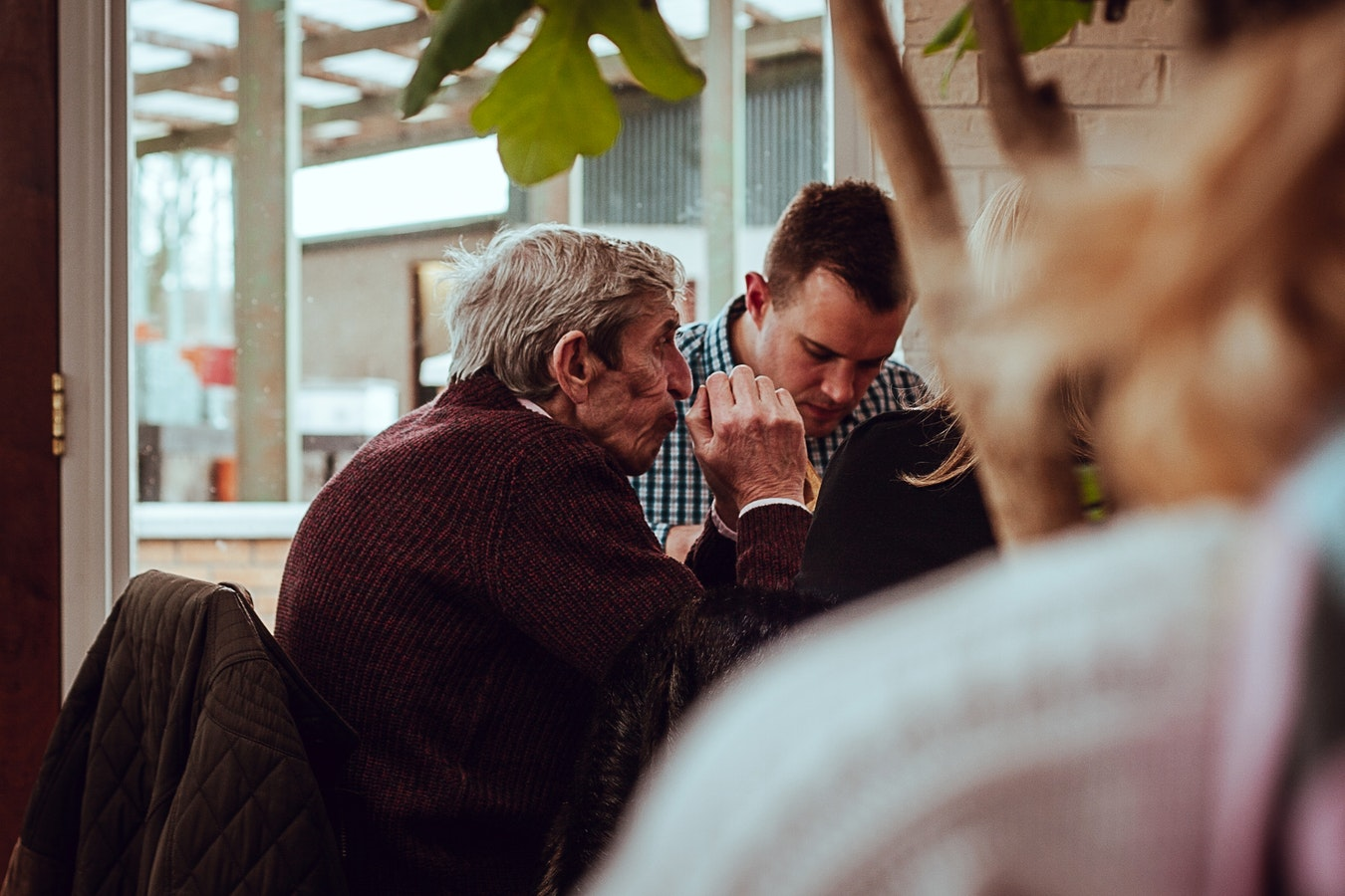 An older man sitting at lunch. Music therapy, even during lunch time, is beneficial for seniors with Alzheimer's.