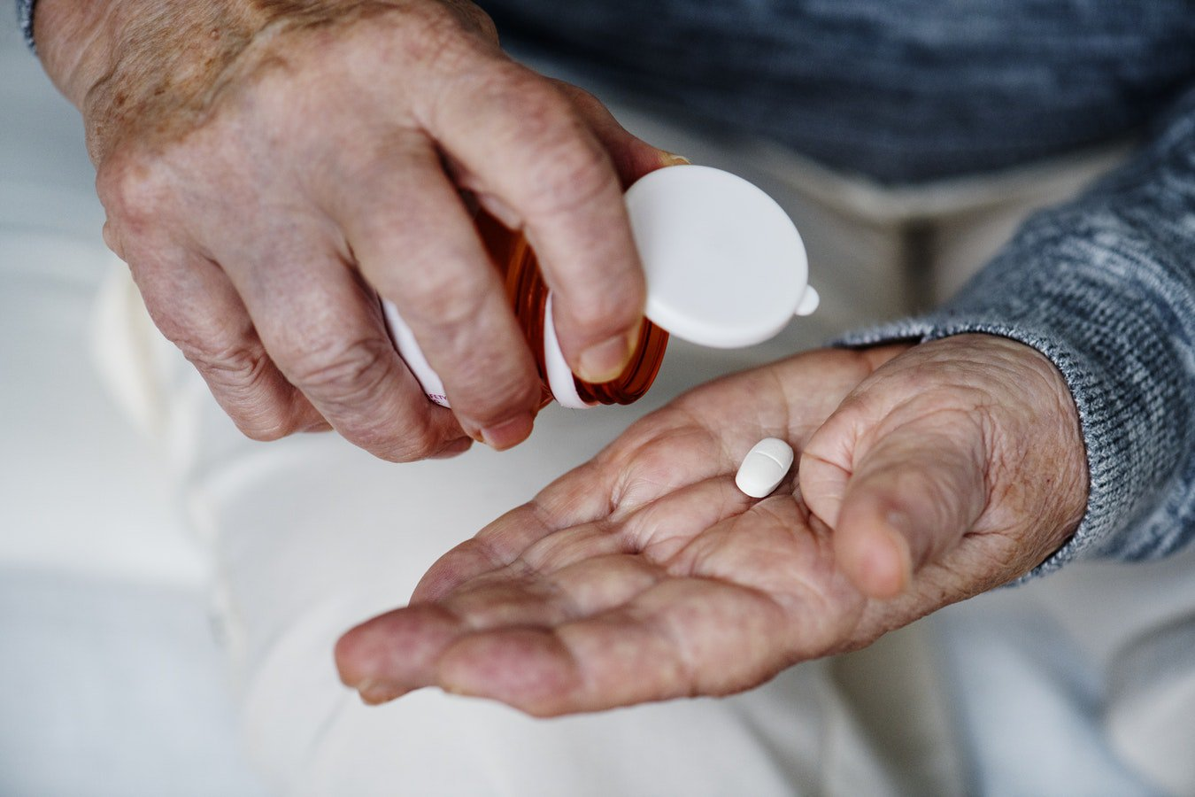 An older man taking his prescription medicine