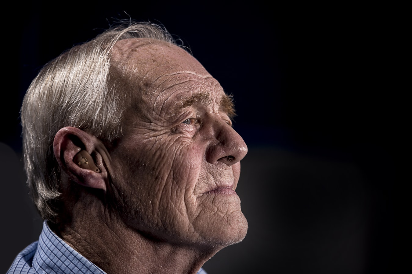 An older man wearing a hearing aid because he suffers from hearing loss