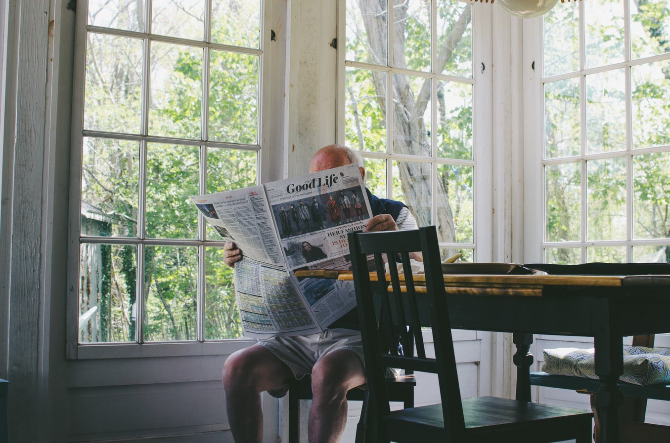 An older man with early stage alzheimers disease sitting at the table reading the newspaper