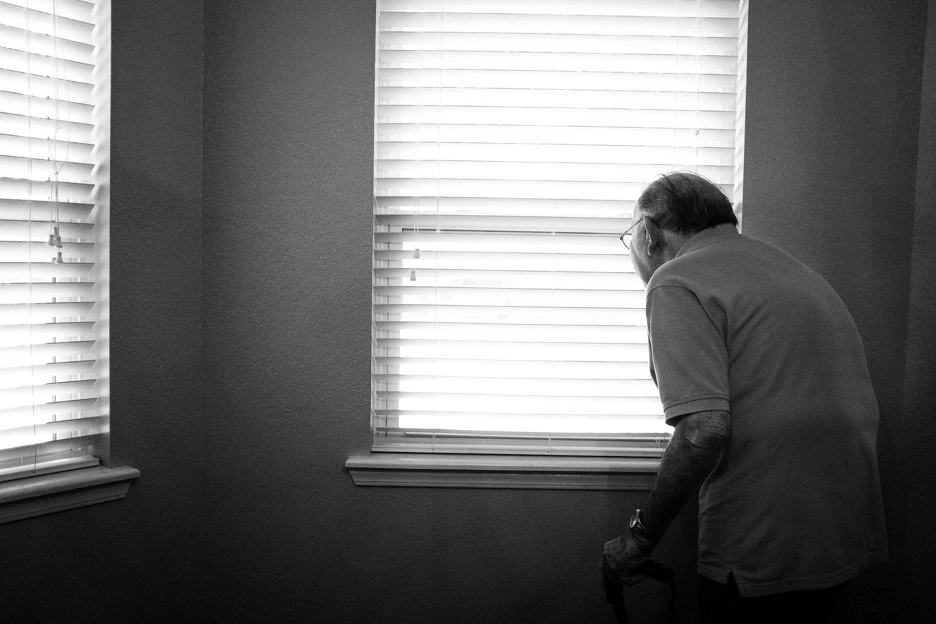An aging parent standing by the window and looking outside.