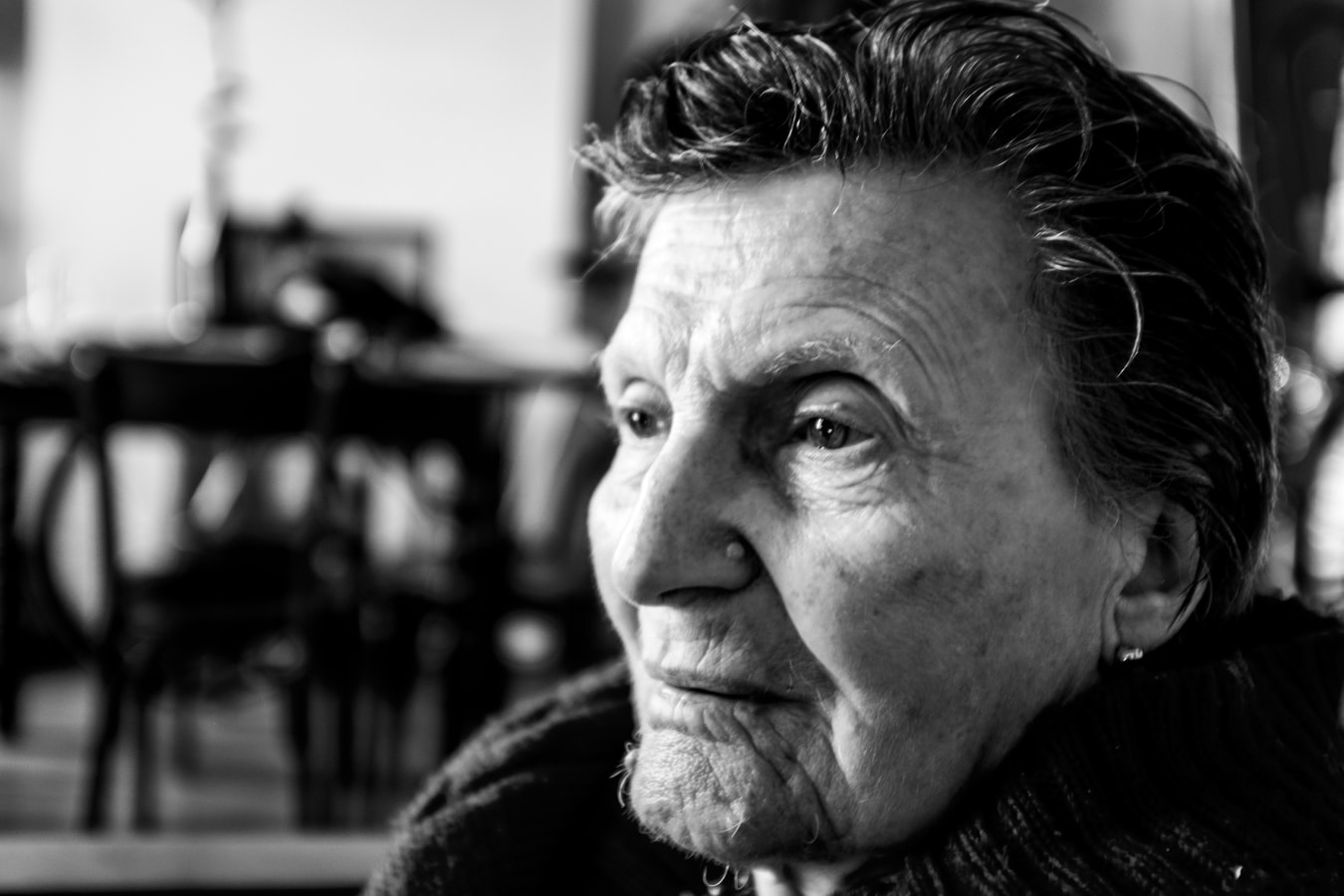 An older woman looking in the distance. PTSD in seniors is becoming more common