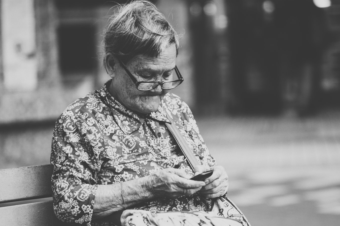 An older woman scrolling on her cell phone.