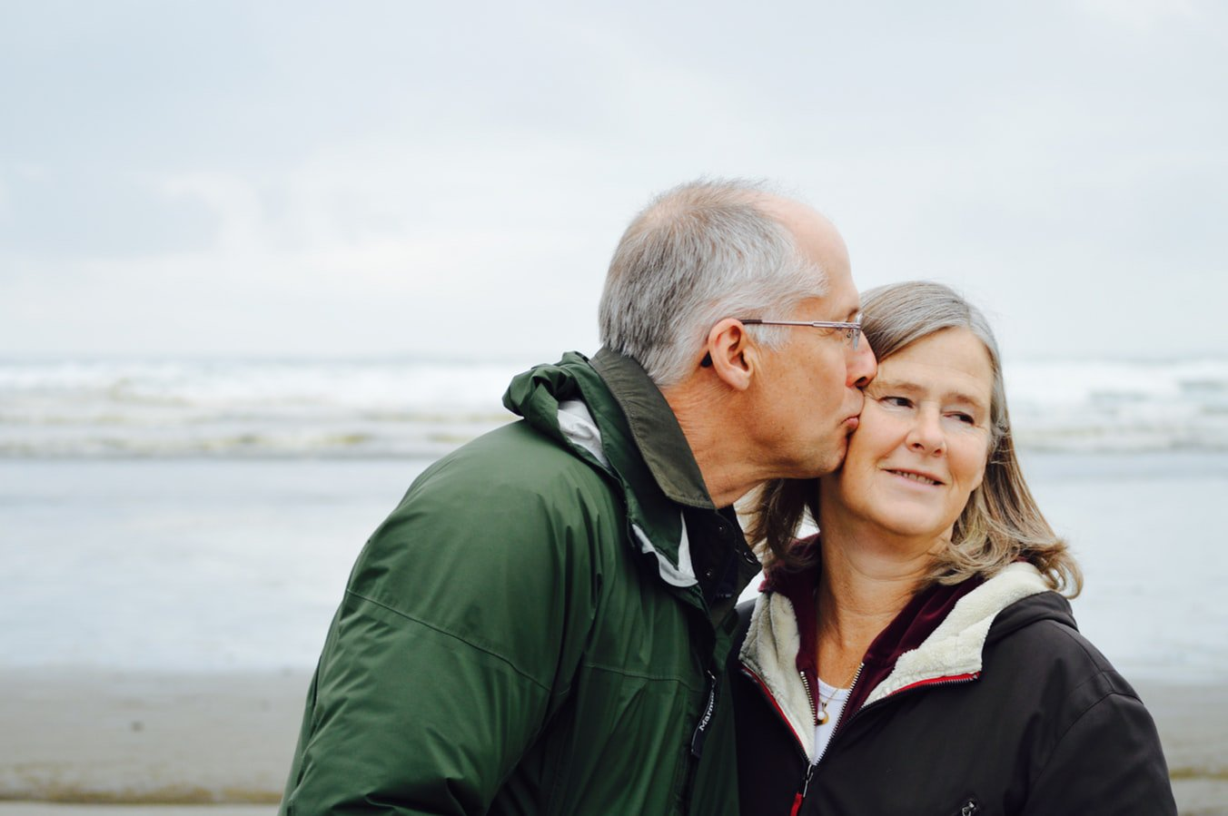 An older woman with Alzheimer's being kissed on the cheek by her husband