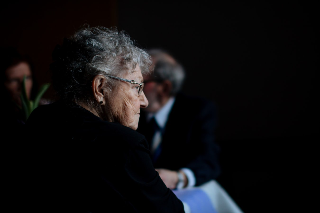 An older woman with Alzheimer's sitting in a room with friends