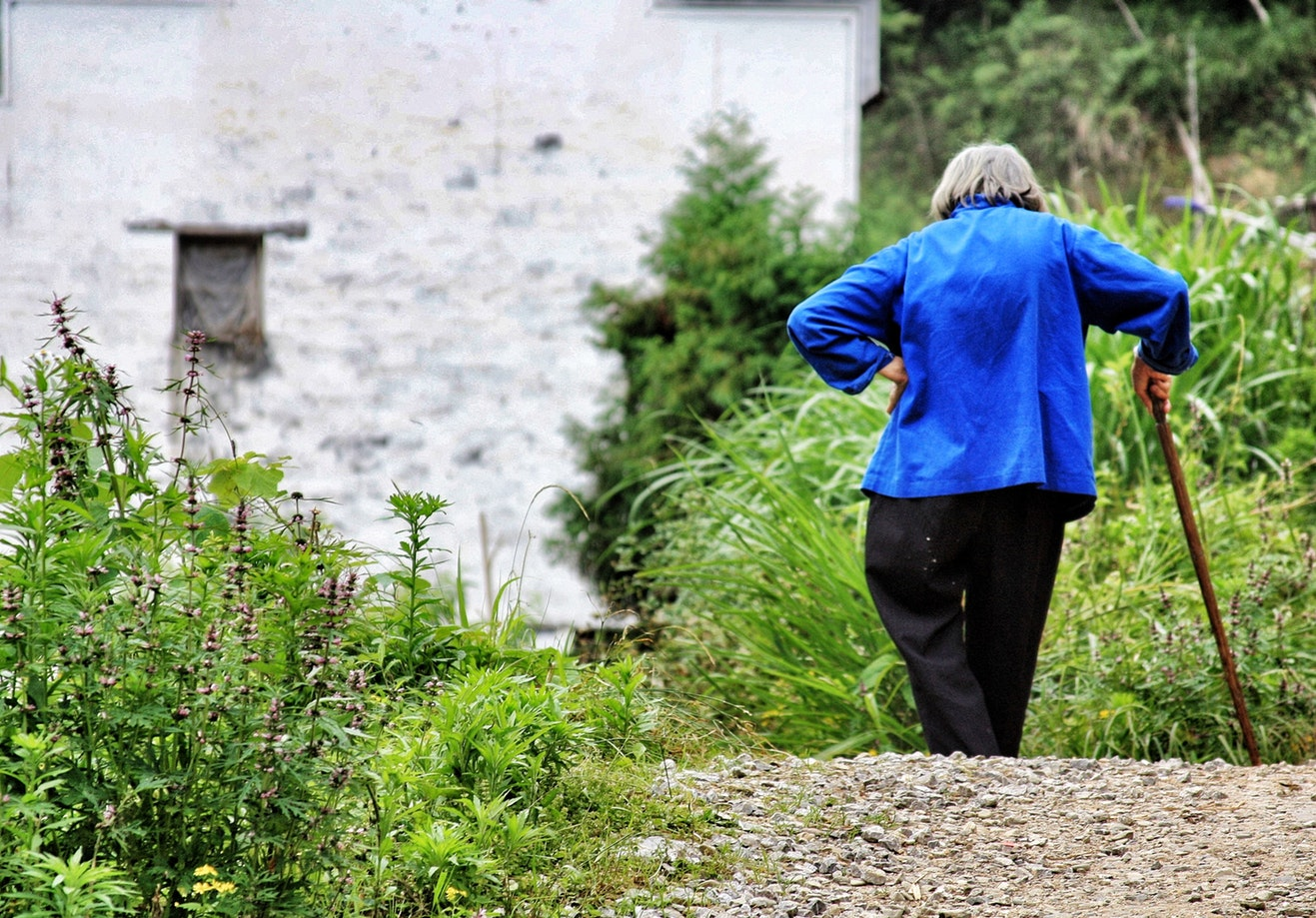 An older woman with alzheimers walking outside with a cane