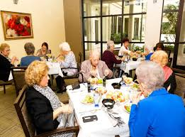 A group of four elderly women eating at a table inside a senior living facility