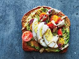 A piece of toast lathered with a sliced boiled egg, avocado spread, tomatoes, lettuce, and olive oil.