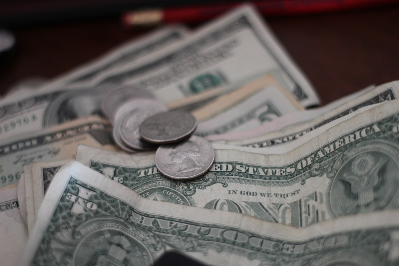 Dollar bills and change laid out on a table. It is important to learn how seniors can stretch their dollar as they age.