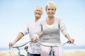 Two seniors smiling and riding bikes.