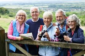 Five seniors smiling on camera while hiking-They are promoting great senior health