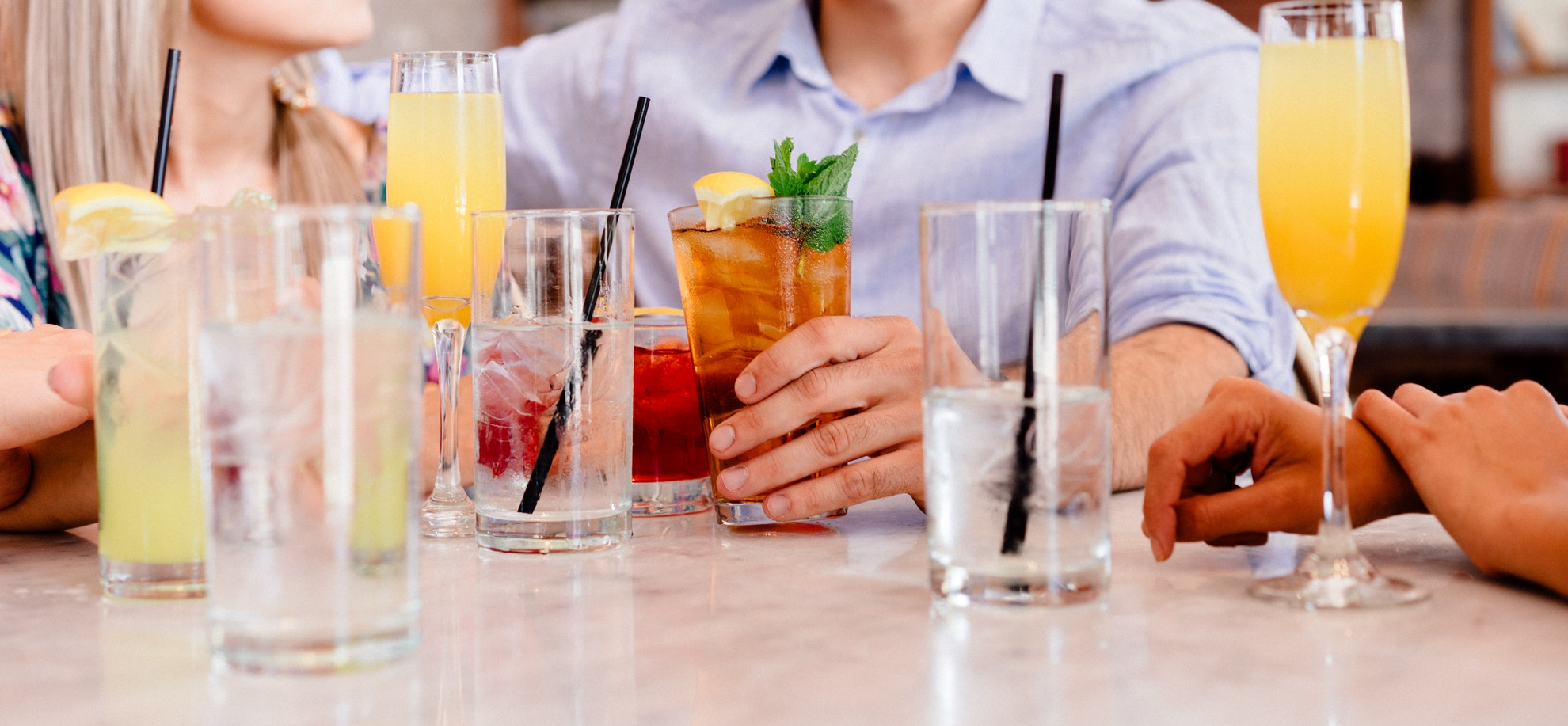 Individuals at lunch enjoying different alcoholic beverages