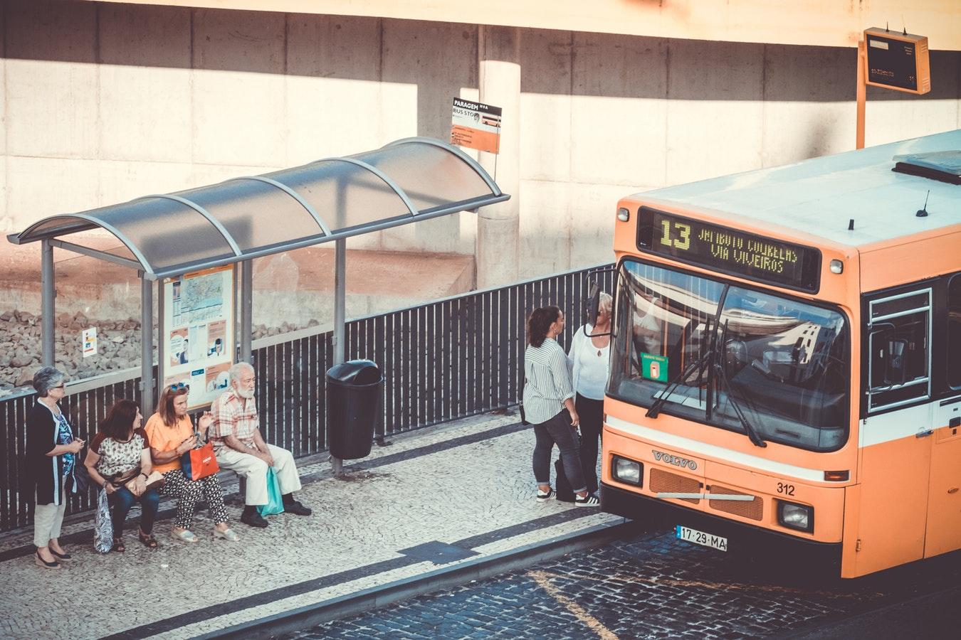 Non driving seniors waiting at a bus stop.