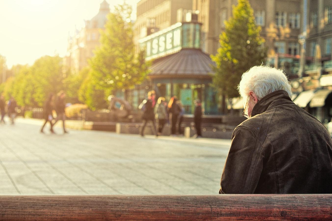 An older gentleman sitting alone on an outdoor bench.
