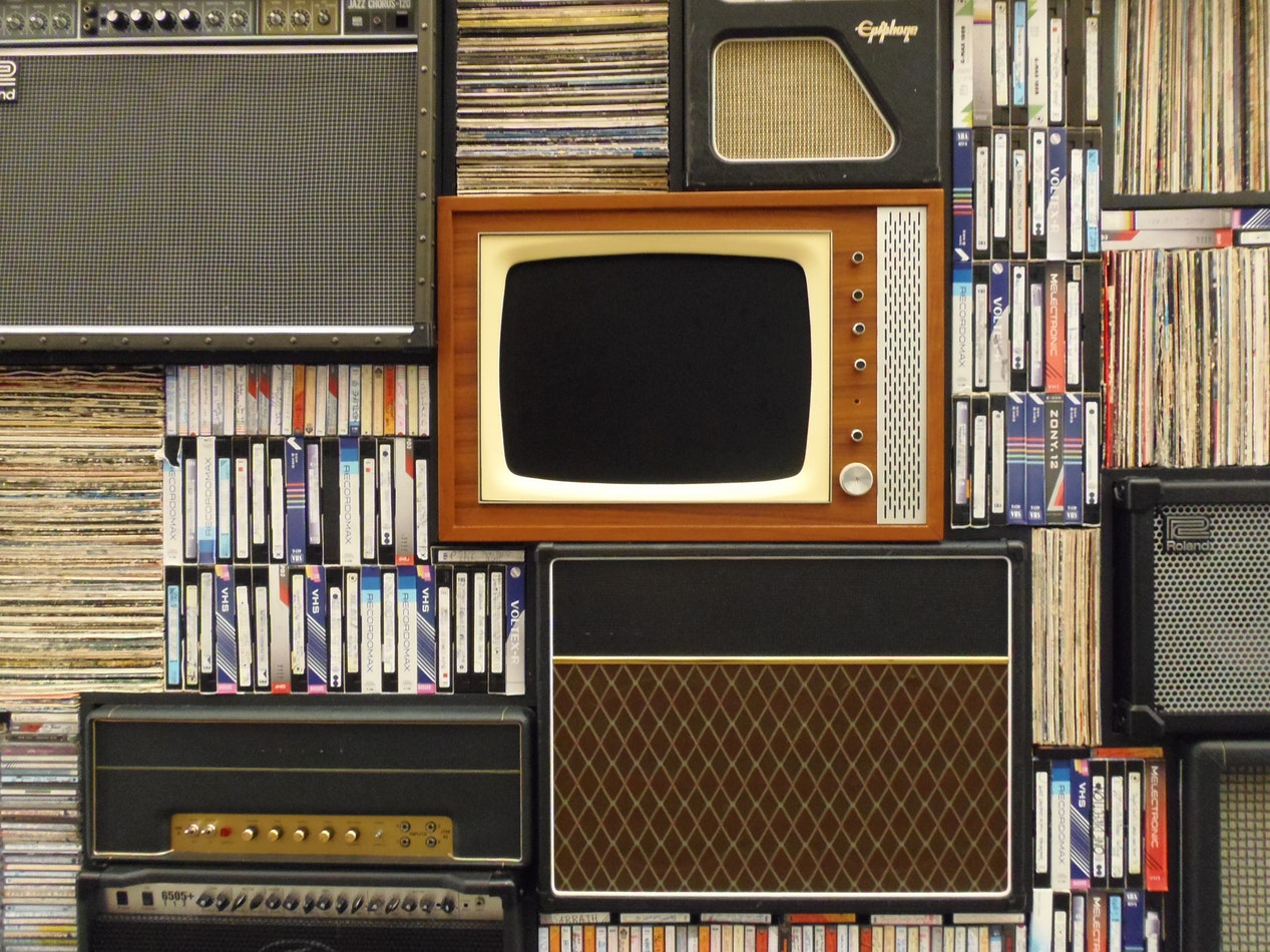 Radios and Tvs on a wall with different records and vhs tapes. Music is a great way to assist with healthy aging.