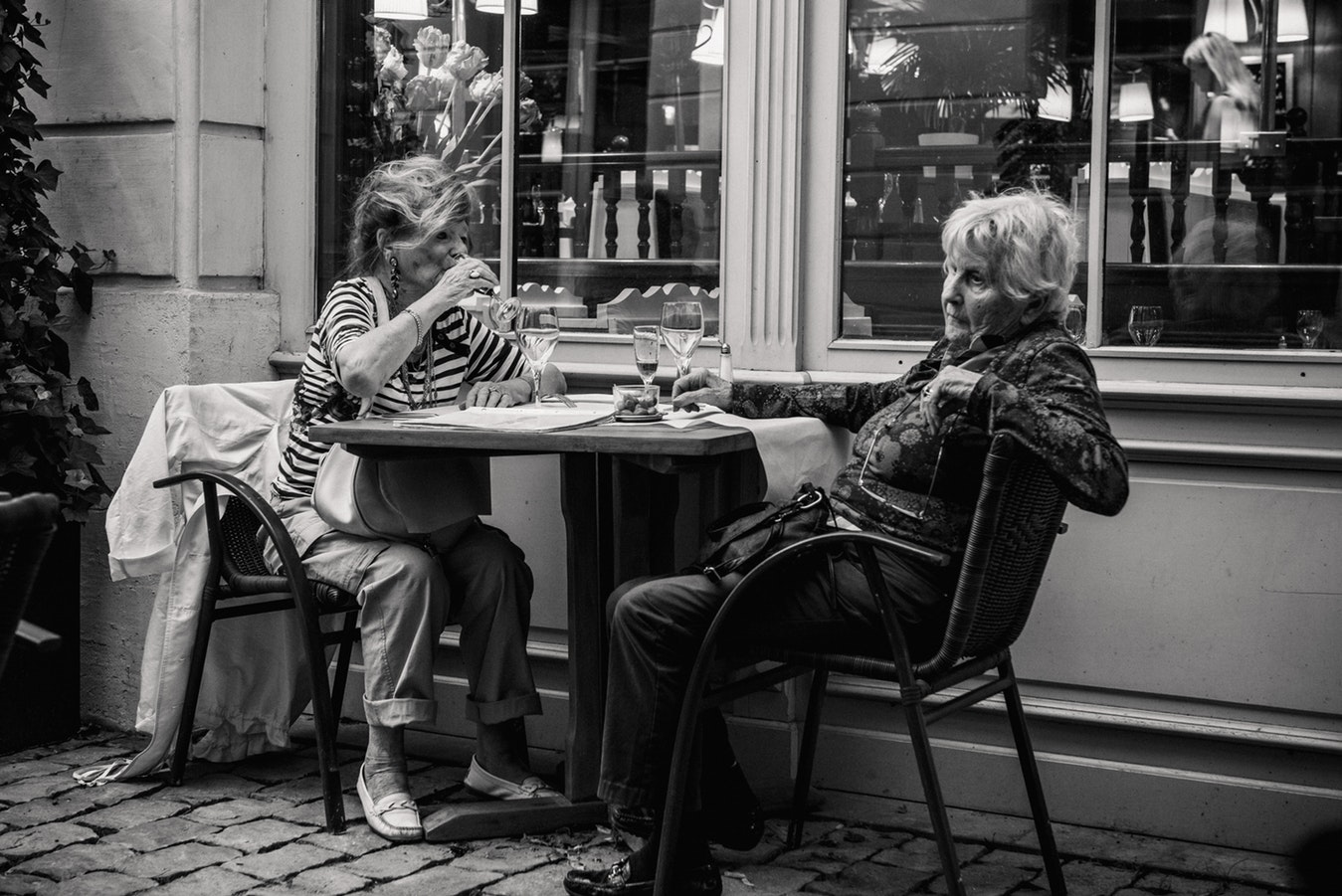 Two elderly woman sitting at a cafe at night