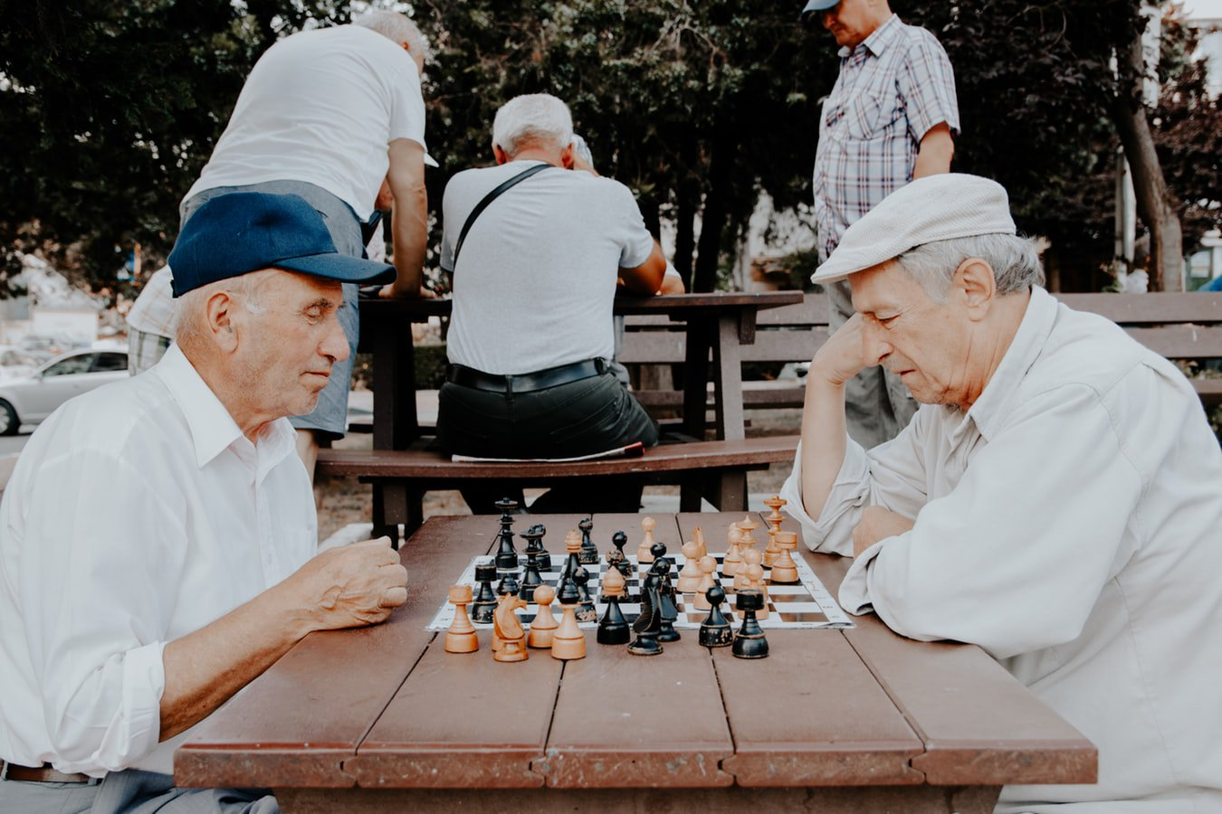 Two older men sitting outside of their assisted living facility enjoying a game of chess