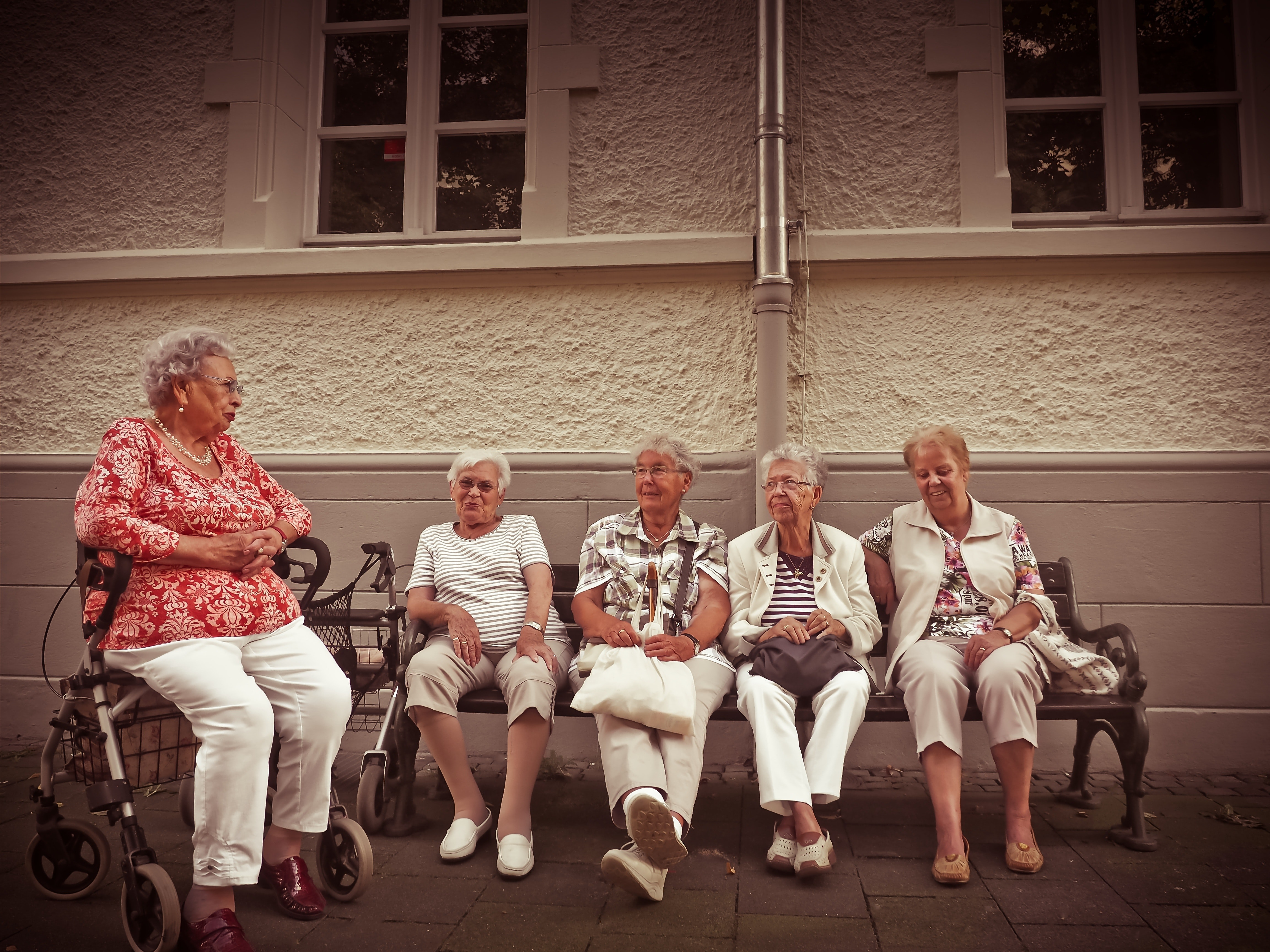 A group of senior women sitting together discussing secrets to living longer.
