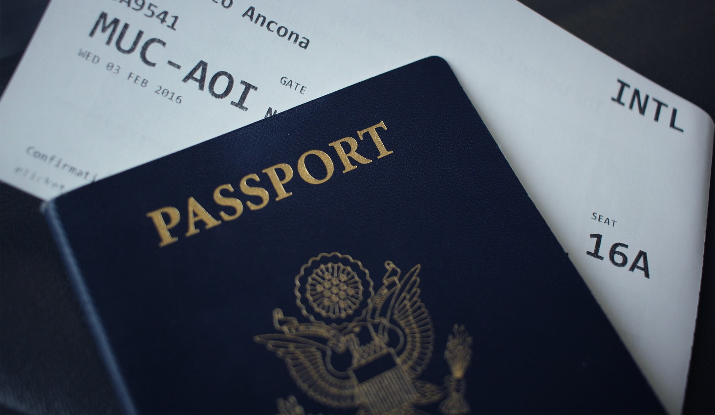 an individuals passport on top of their boarding pass to a flight abroad