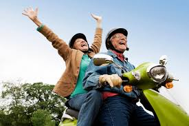 An elderly couple riding a moped on a road while smiling and laughing