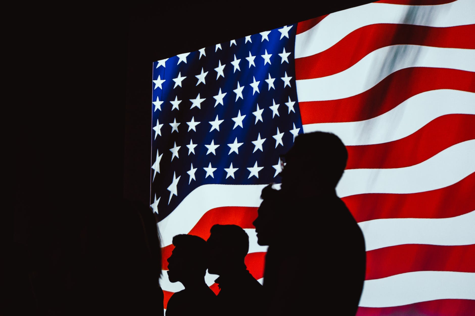 The United States Flag with Veterans, who are supported by the VA, saluting in front of it.