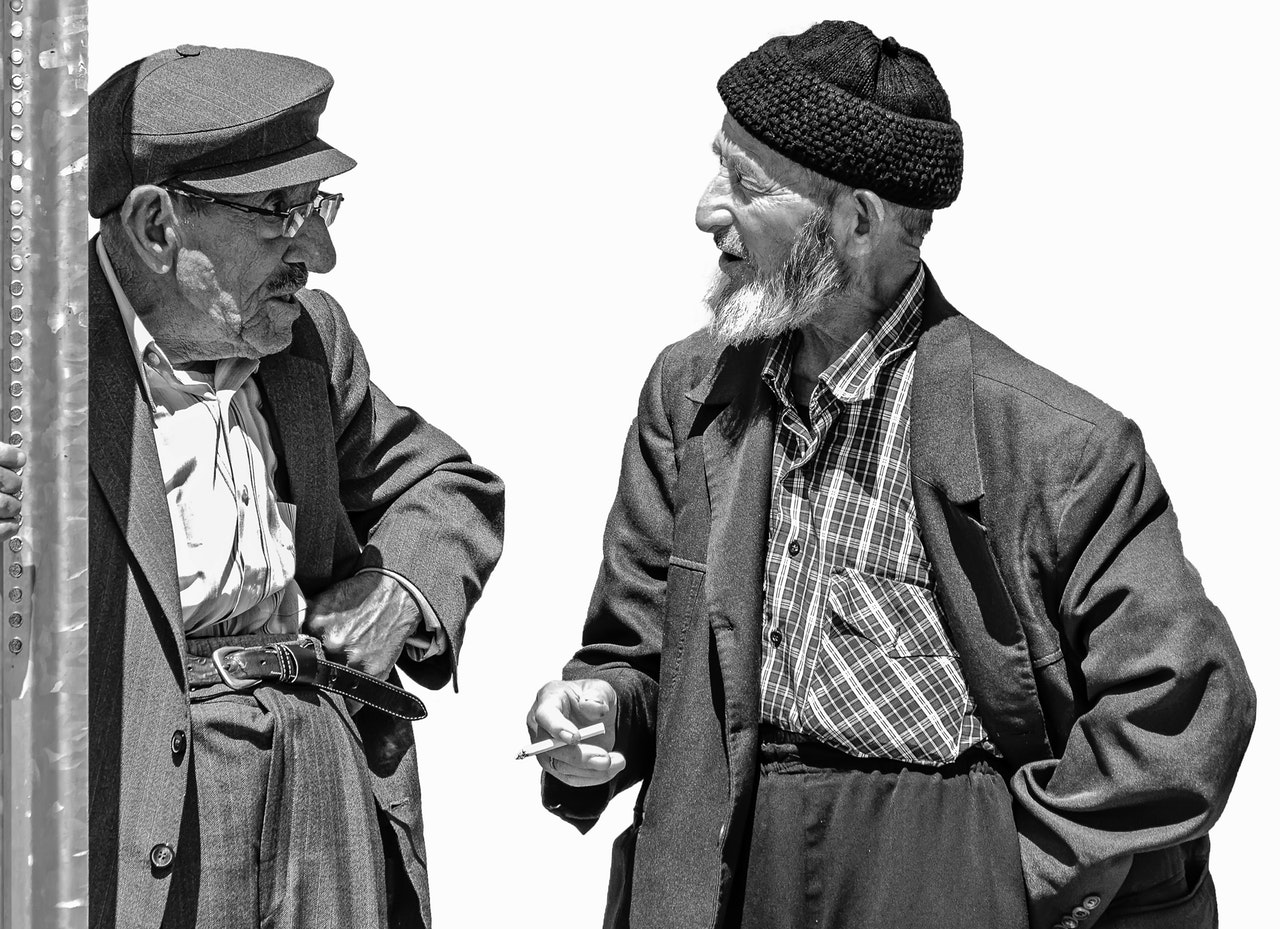 Two older men talking to each other.