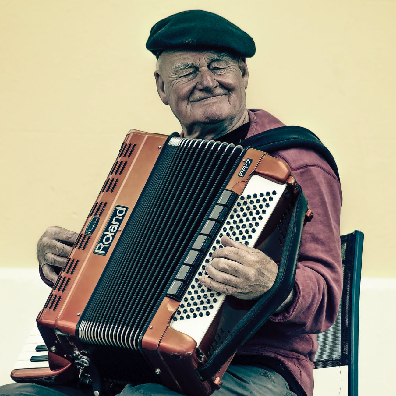 A senior man playing an accordion, busting the myth that seniors aren't creative.