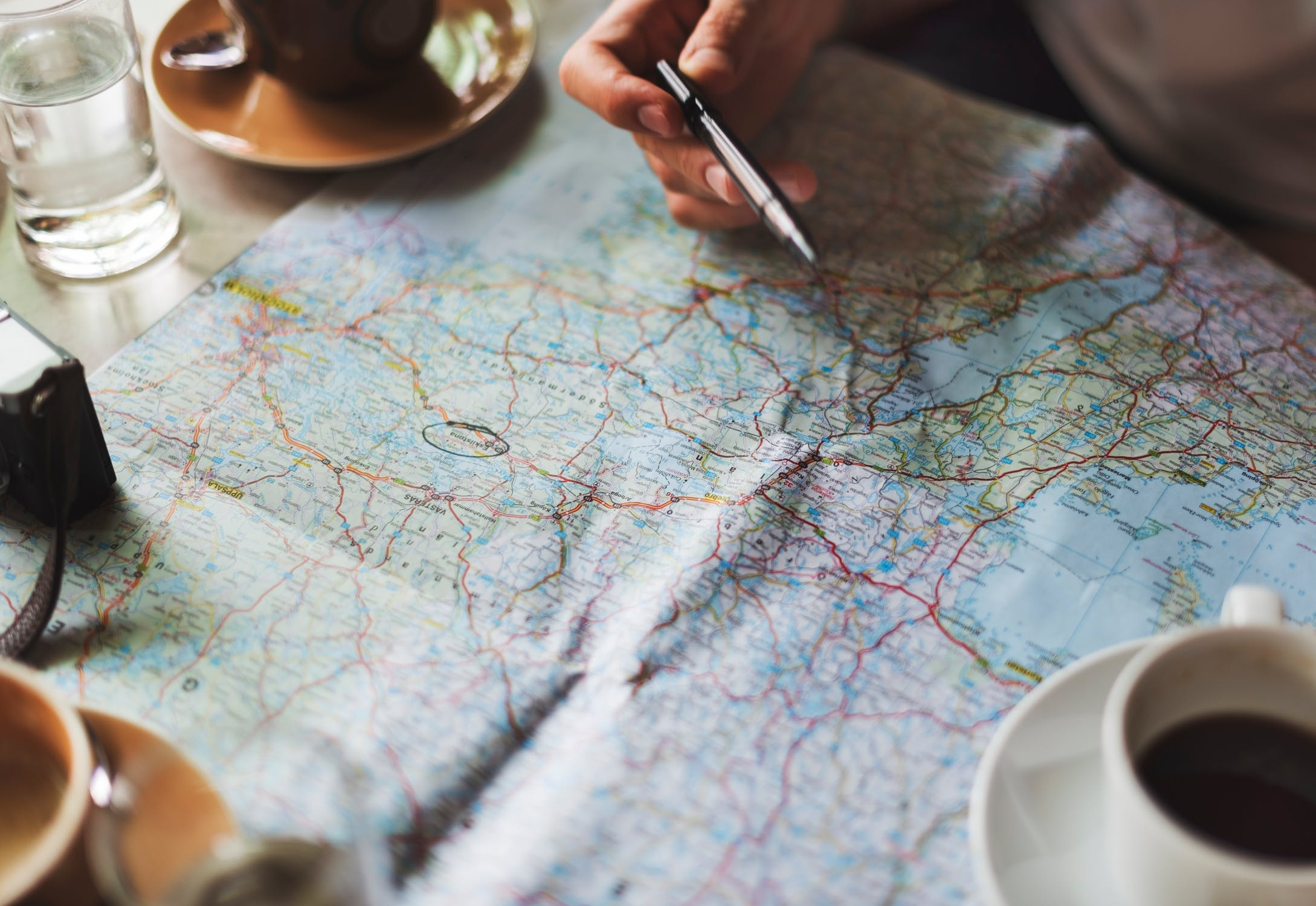An individual looking at destinations on a map. It is important to pick destinations carefully when traveling with family members with memory loss.