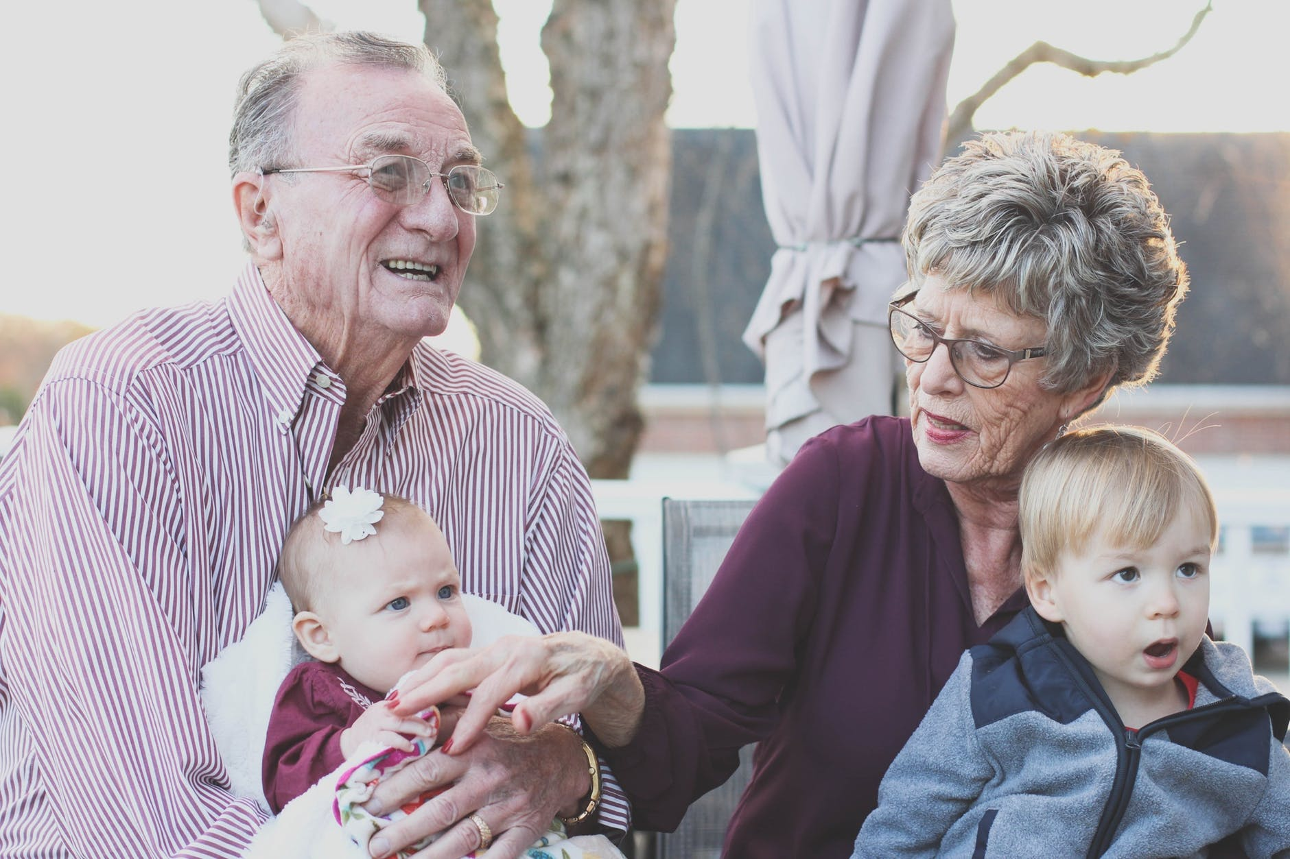 Grandparents holding their grandchildren. If you are interested in learning if your parents should move in with you, learn more here.