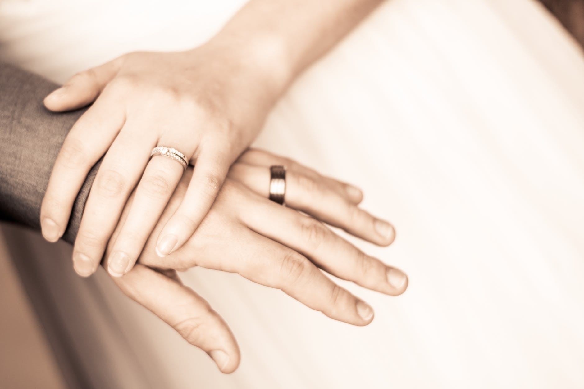 A couple holding their hands over each others showing their wedding bands.