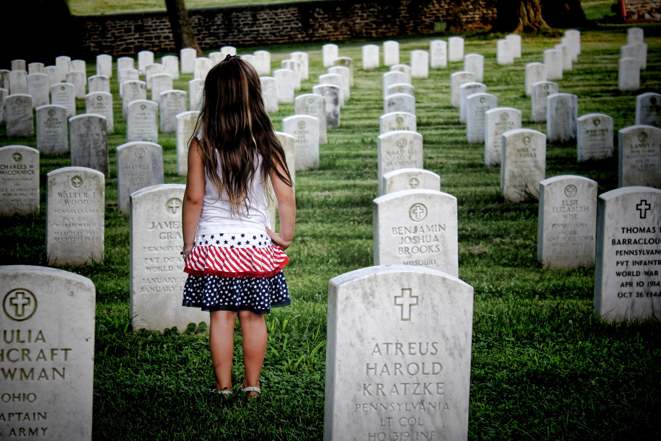 A young girl remembering her loved one at a veterans cemetery.