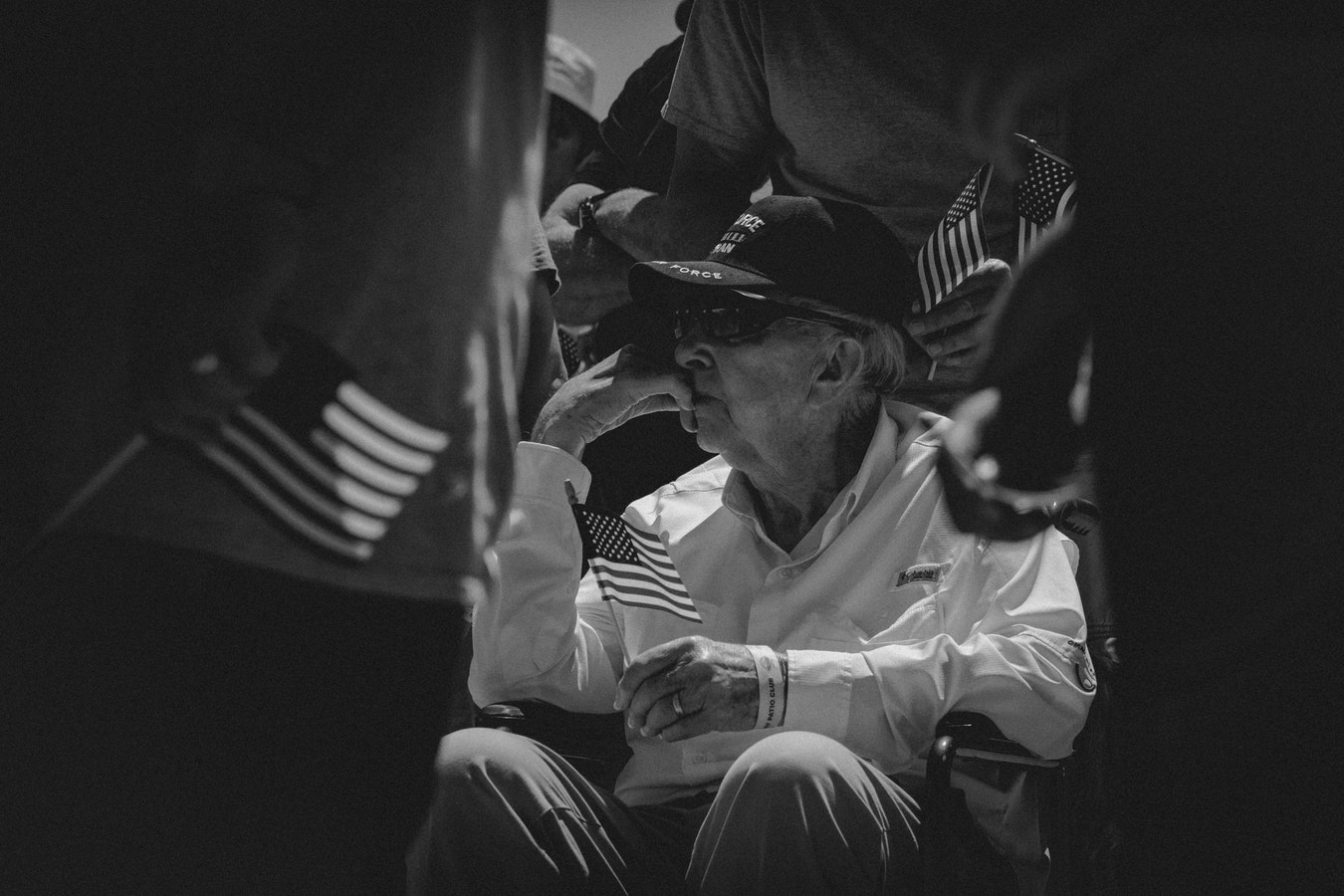 An older veteran sitting and holding an american flag.
