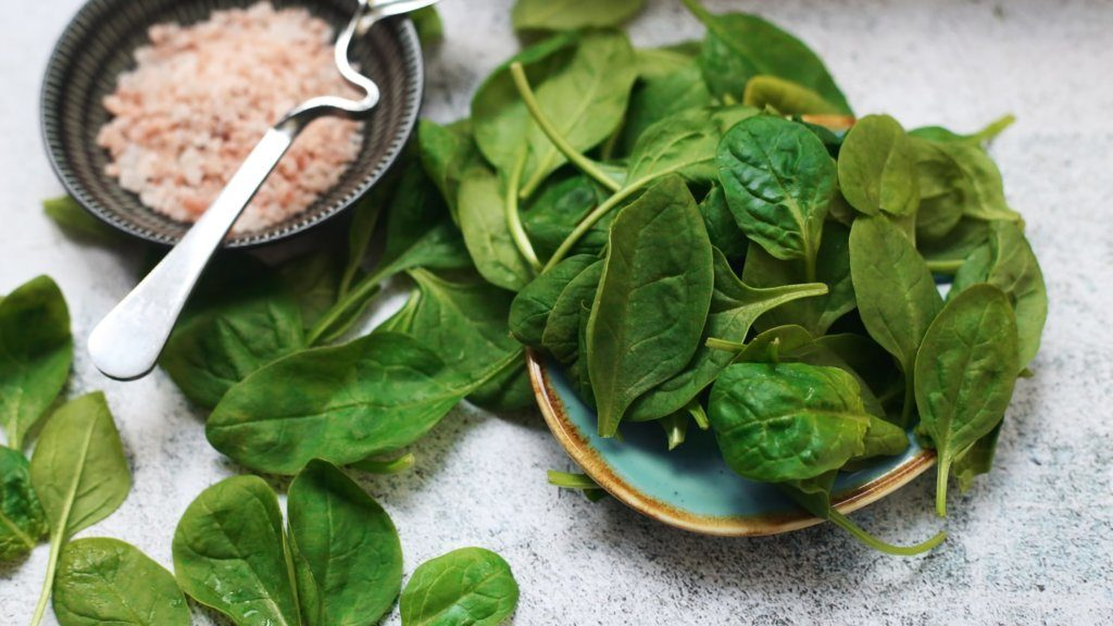 A bowl of spinach next to salt.
