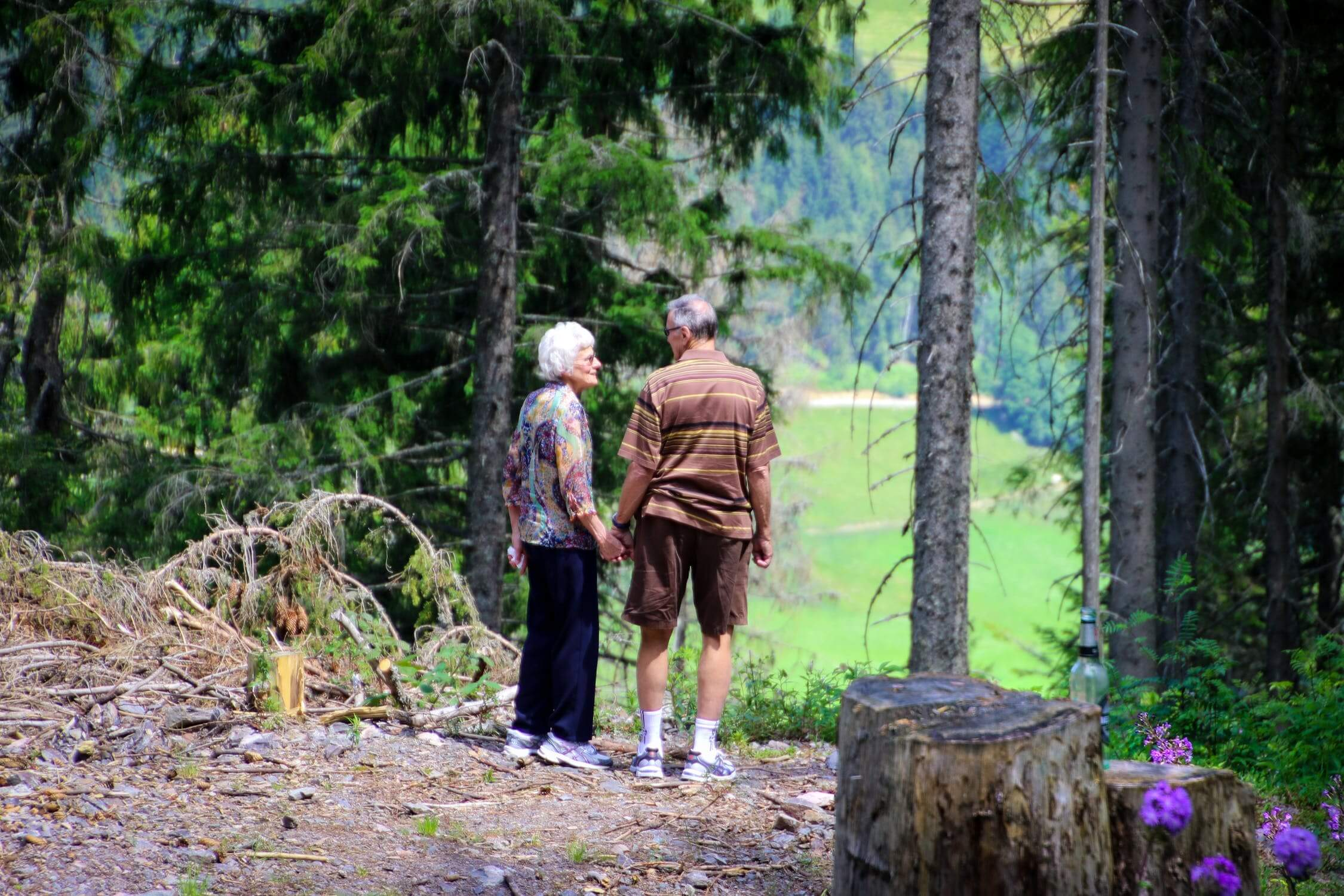 An elderly couple on a hike. They are talking about the pros of an assisted living facility