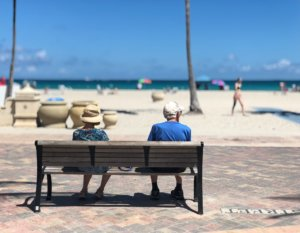 An older couple enjoying their time at the beach. A day at the beach can improve your health.