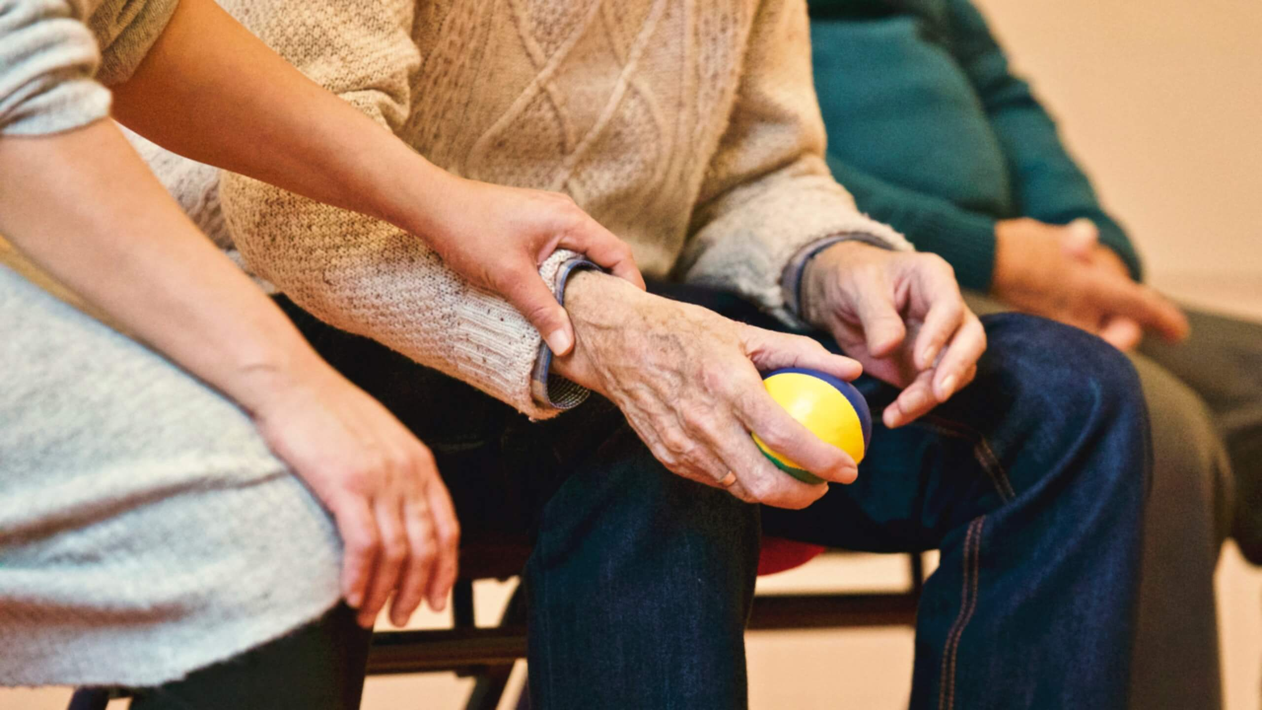 A caretaker working with a resident in a senior living facility.