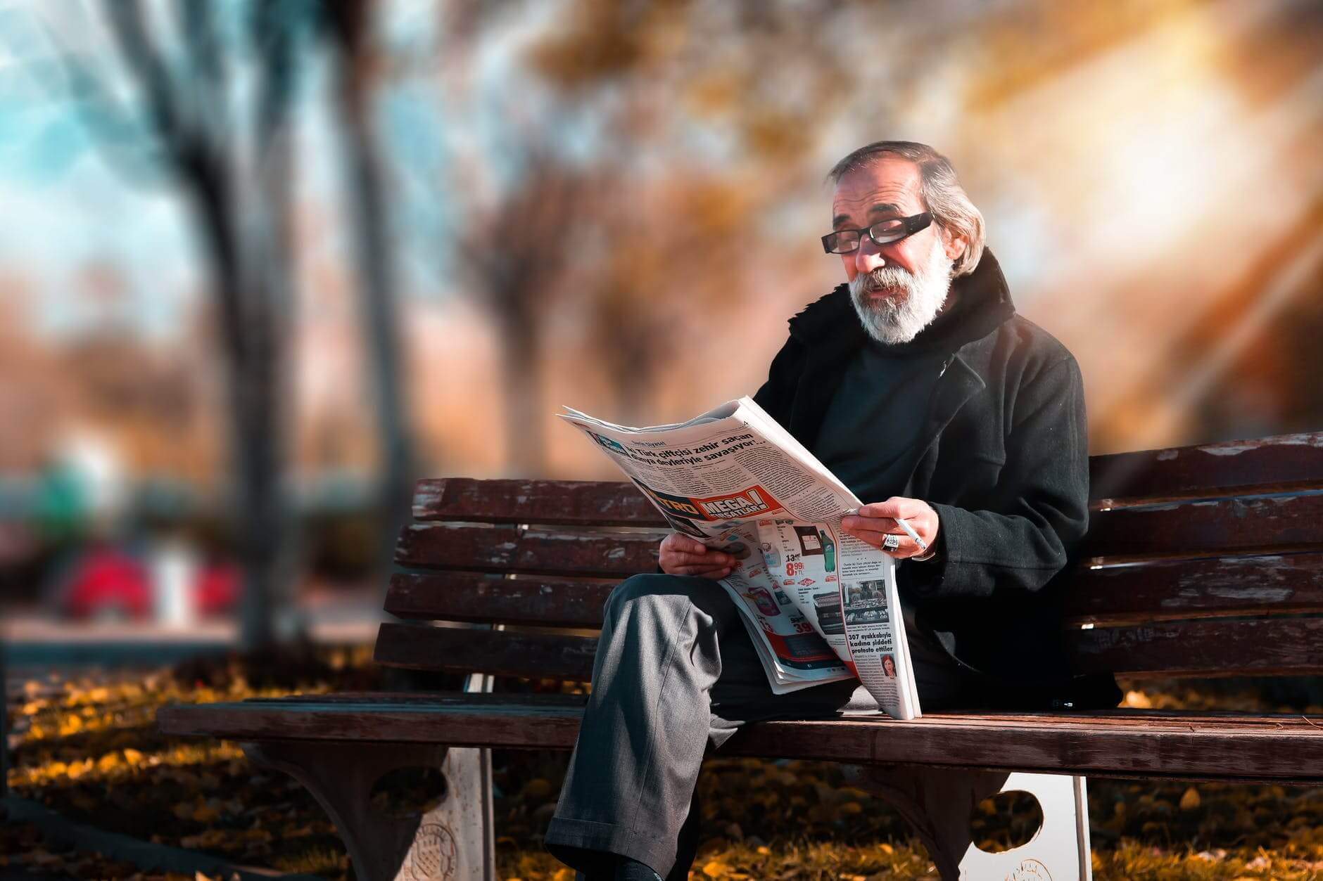 A man sitting on a bench reading a newspaper and learning about the benefits of reading as we age