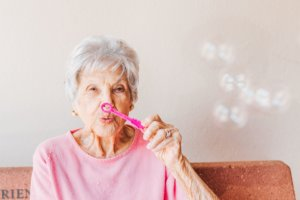 A woman having fun and blowing bubbles during her stay at a respite care facility