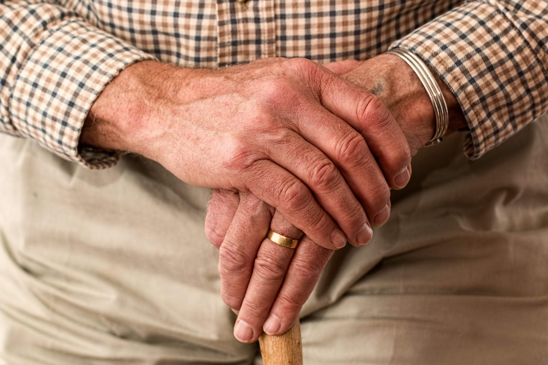 An old man holding his cane while thinking about the benefits of the flu shot for seniors