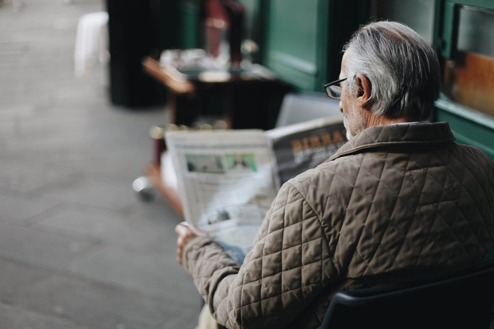 An older man reading a newspaper talking about the benefits of reading as we age