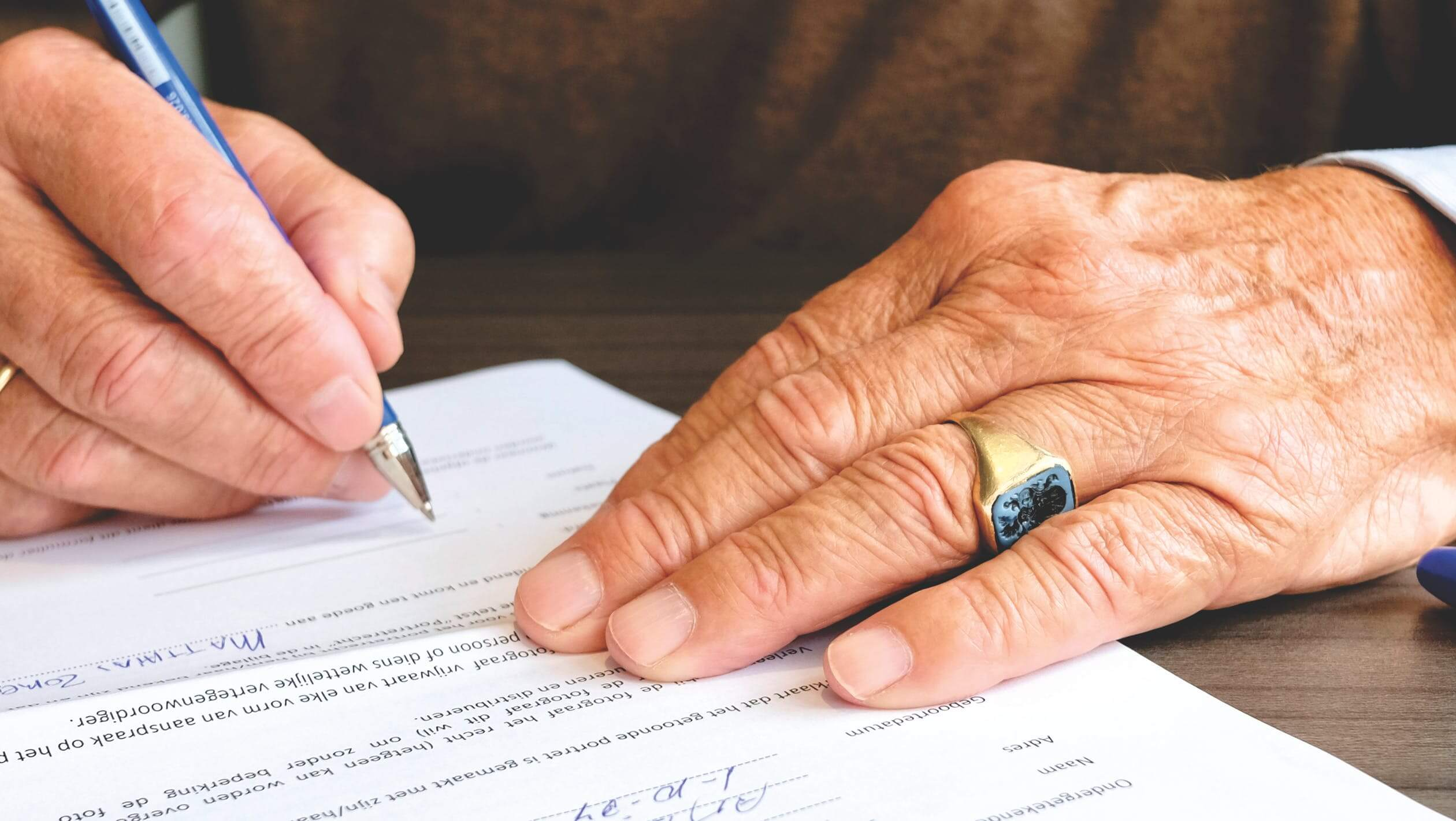A man signing a legal document. Having legal paperwork is important when you move your loved one to an assisted living facility.
