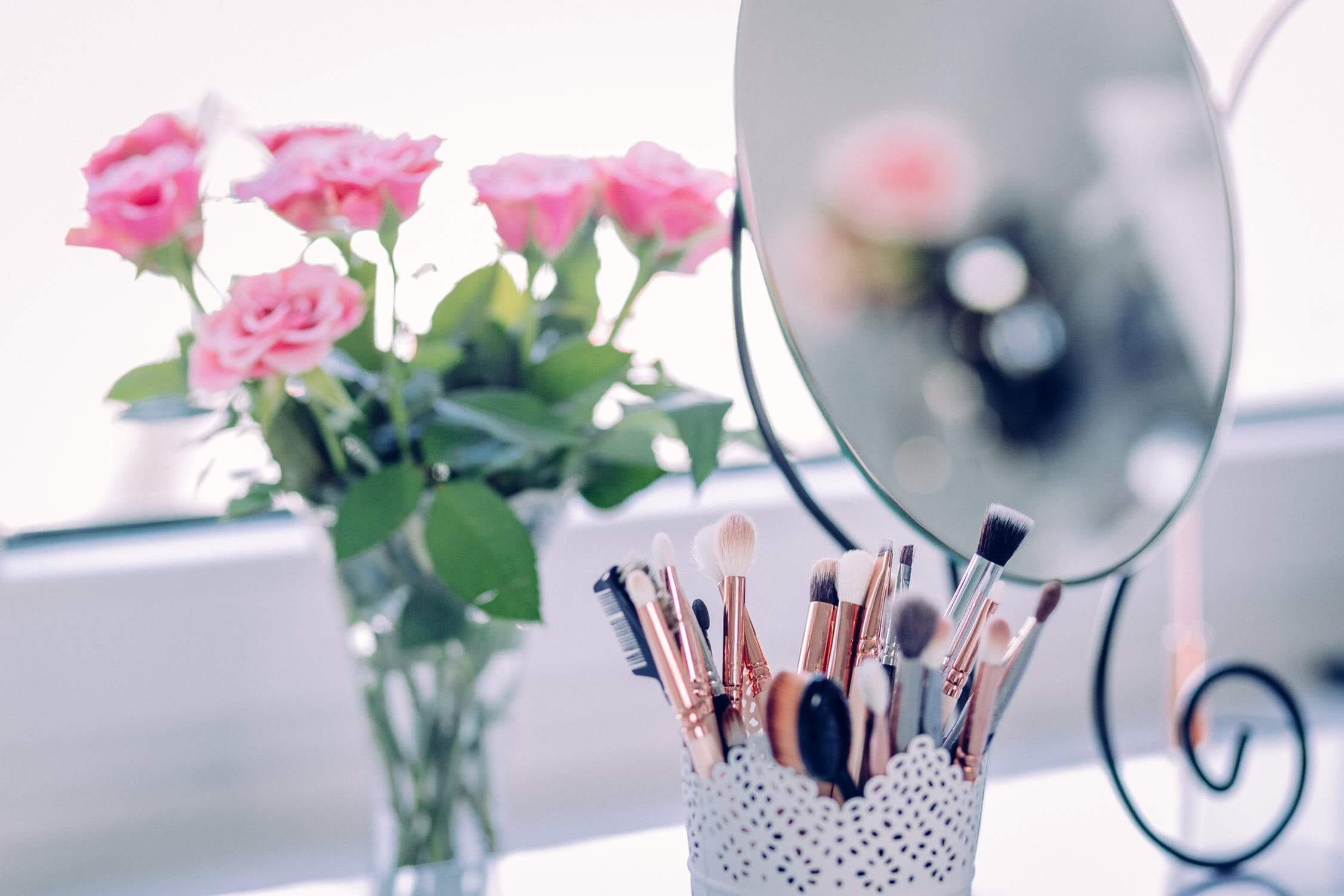 A mirror with makeup brushes in front of it. Many women with skin issues, like wrinkles, will wear makeup to hide them.