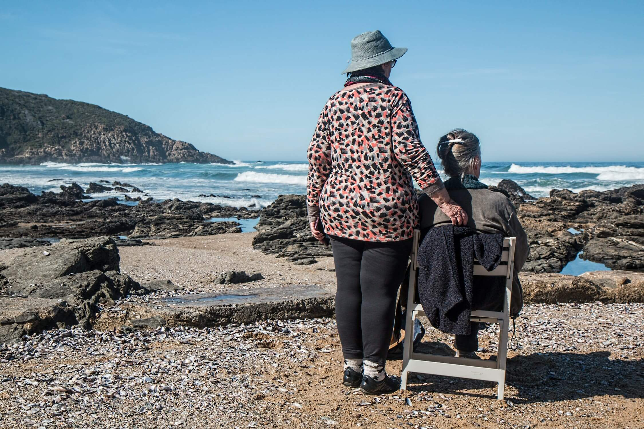 A woman standing next to her friend who is sitting and watching the ocean. Exercise and staying busy is helpful in preventing sundowning.