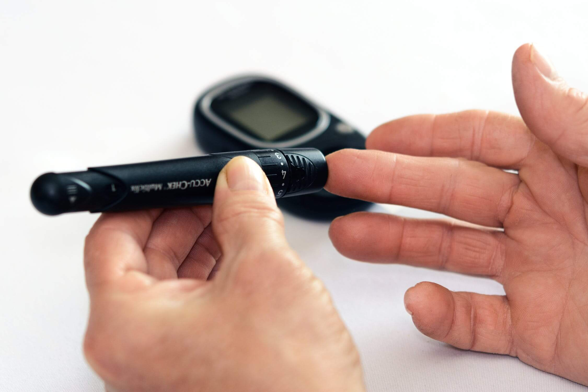 An individual with diabetes poking their finger with a glucose monitor.