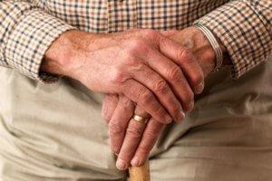 An older man holding a cane to help him walk