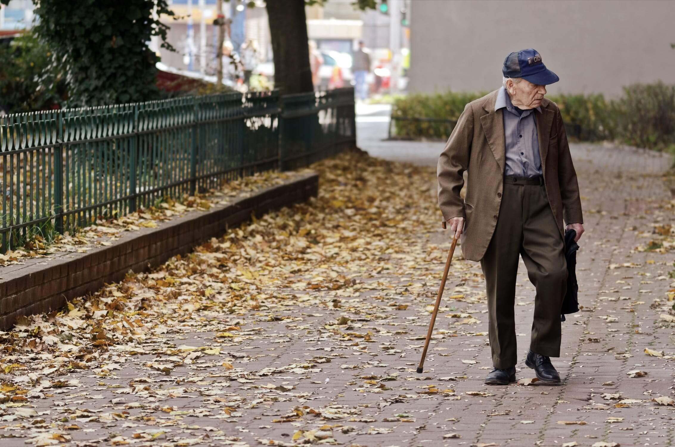An older man walking and thinking about moving into an assisted living facility