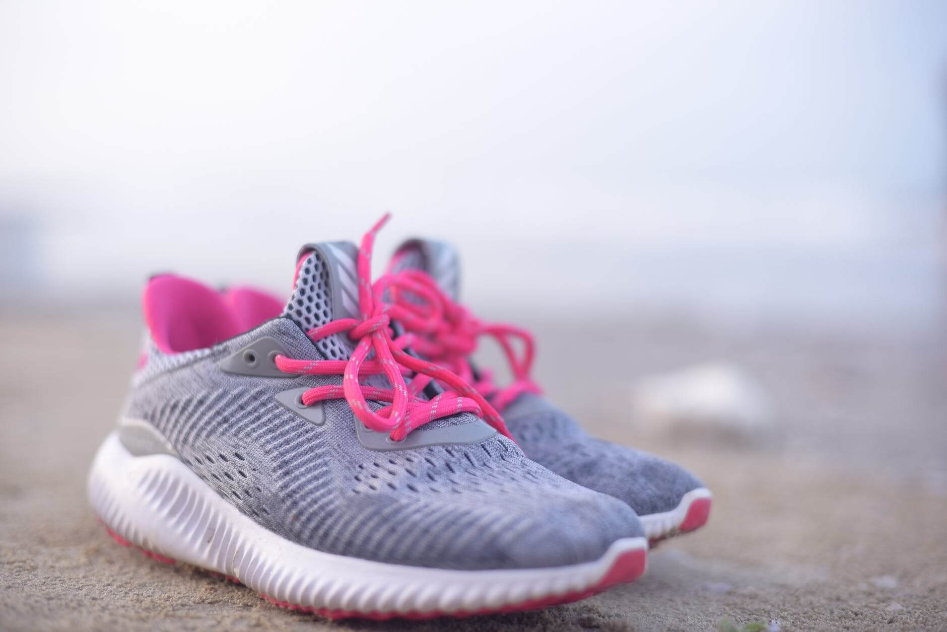 A pair of pink and grey tennis shoes worn during a workout