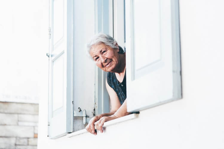 A woman looking outside her window and smiling