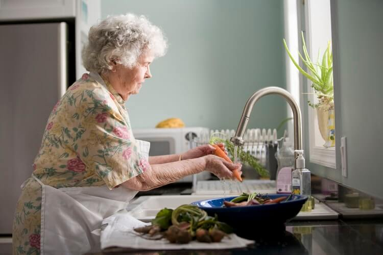 A woman washing vegetables in the sink before making dinner