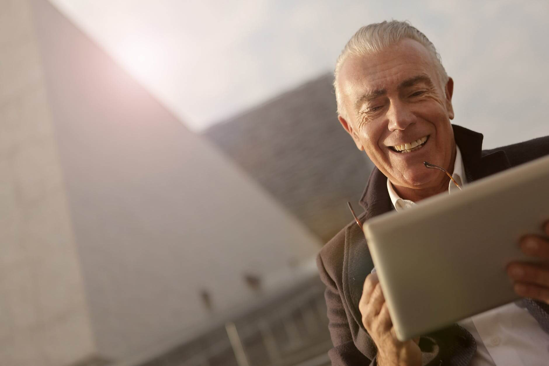 An older man smiling while watching tv on his tablet